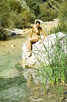 Young woman sitting on rocks by lake
