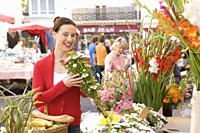 Pretty young woman buying flowers