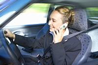Happy businesswoman using mobile phone while driving car