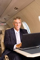 Businessman using laptop computer on aeroplane, smiling, portrait