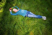 Teenage girl 11_13 lying in grass with eyes closed, elevated view full frame