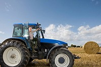 Farmer stepping down from tractor in hay field (thumbnail)