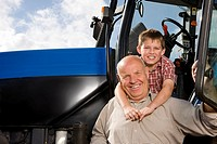 Portrait of boy hugging grandfather by tractor