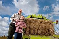Farmer and grandson standing near machinery and straw bale