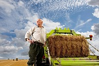 Portrait of farmer standing near machinery with straw bale