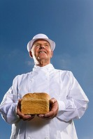 Portrait of baker in white uniform holding loaf of bread