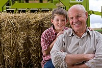 Portrait of farmer and grandson on tractor with straw