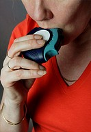 Woman using asthma inhaler.