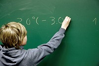 School kid making calculations on a blackboard.