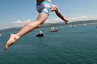 Close up of the legs of a man leaping off the jetty in Aberdyfi into the Dyfi Estuary, summer afternoon, Wales UK