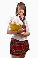 Teenage girl wearing her school uniform holding her books