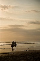 Couple walking on beach at sunset, Legian, Bali, Indonesia