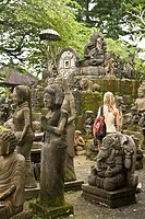 Tourist observing statues for sale near Ubud, Bali, Indonesia