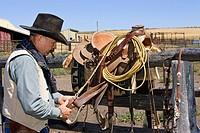 Cowboy preparing saddle, wildwest, Oregon, USA