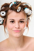 Pretty young brunette woman with curlers in her hair