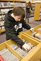 Ricky Lynch, 18, from Berkley, looks through the music CDs.  The library in St. Ann on St. Charles Rock Road