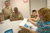 Tammy Ney, right, teaches a first aid class to scouts Randall rootz, Greg Lane, and Tyler Ney, left to right.  Boy scout troop 942 at St. Andrew Unite...