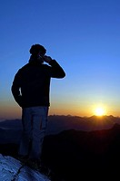 Man with mobile phone at sunrise on a mountain top, Breitenstein Mountain, Bavarian foothills, Wendelstein Group, Upper Bavaria, Bavaria, Germany