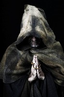 Hooded monk wearing habit, praying