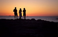 three people standing on the shore watching the sunset