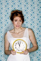 The 11th hour, young bride illustrating various concepts relating to wedding day, studio blue background. Denver, Colorado, USA
