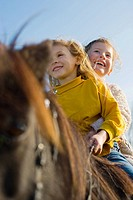 Girls riding a shetland pony
