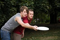 A gay couple playing frisbee