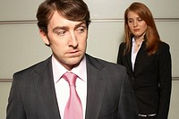 Close_up of a businessman looking behind at a businesswoman