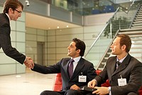 Two businessmen shaking hands with another businessman sitting on a couch