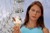 Portrait of a young woman holding an ice_cream cone with a ferris wheel in the background