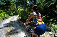 A woman bicycling on a bicentennial Bicycle Track on West Island, Cocos Islands, Australia