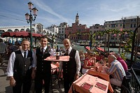 Waiters and people on the terrace of Cafe Saraceno near Rialto Bridge, Venice, Veneto, Italy