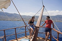 A couple standing at the bow of a ship, Neptun Pirate boat trip, by Kaleidoskop Turizm, and coast, Kyrenia, Girne, Cyprus