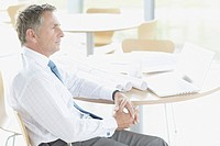 Businessman sitting at table with blueprints