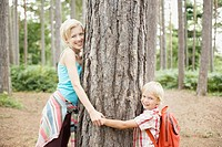 Mother and son hugging tree in woods