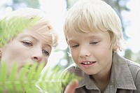 Mother and son examining fern leaf