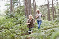 Mother and son running in woods