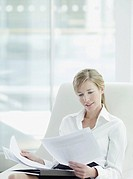 Businesswoman reviewing paperwork in office
