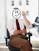 Businessman holding picture of angry face (thumbnail)