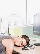 Businesswoman sleeping on computer keyboard