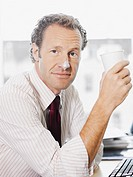 Businessman with coffee foam on nose