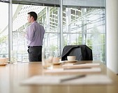 Businessman looking out conference room window