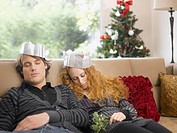 Sleeping couple wearing paper crowns at Christmas