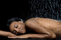 Water falling on nude African woman
