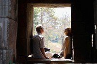 Couple Sitting in Window of Stone Building
