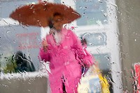 Shopper leaving grocery store with umbrella in the rain (thumbnail)