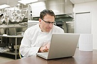 Frustrated chef looking at laptop in kitchen
