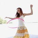 Young woman hula hooping on beach