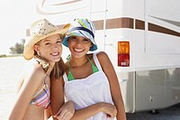 Friends posing near motor home on beach