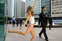 Businessman walking through a modern city and sexy woman running free